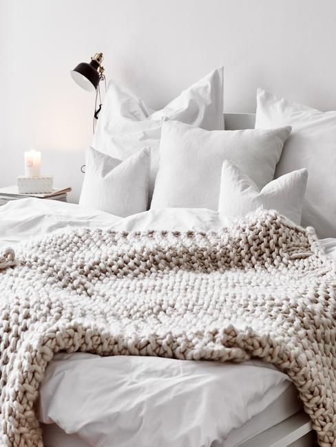 Biała sypialnia z białą pościelom oraz beżowym kocem pledowym