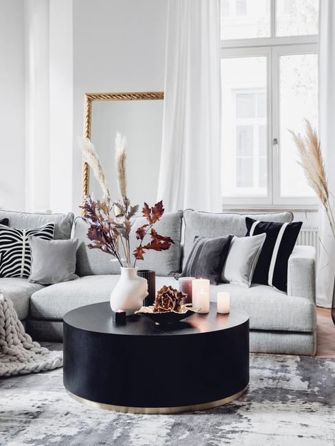 Salon w stylu glam z szarą, narożną kanapą oraz czarnym stolikiem kawowym