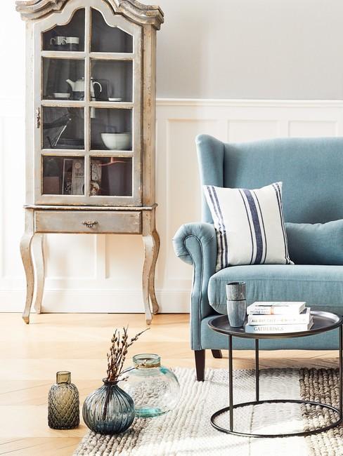 Jasny salon w stylu country z niebieską kanapą oraz drewnianym kredensem