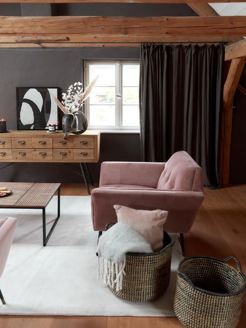 Salon w stylu industrialnym z drewnianym stolikiem oraz komodą, różowym fotelem i białym dywanem