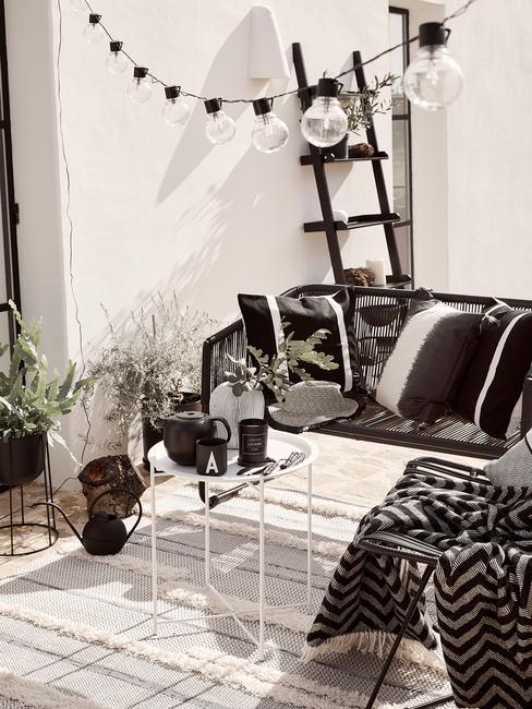 Taras na dachu w odcieniach czarno-białych z dekoracją w kształcie drabiny oraz girlandami przewieszonymi przez taras