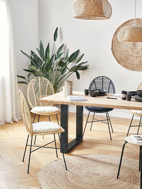 Jadalnia w stylu boho z drewnianym stołem, plecionym dywanem oraz krzesłami w bieli oraz czerni