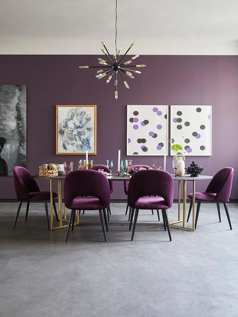 Duża jadalnia z fioletowymi ścianami oraz aksamitnymi krzesłami oraz obrazami na ścianie