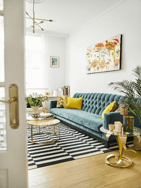 Salon z turkusową kanapą, żółtymi poduszkami, rośliną oraz stolikiem kawowym
