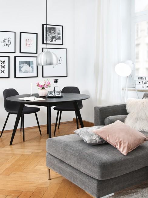 Biały salon z czarnym sotłem i krzesłami oraz szarą sofą i galerią ścienną