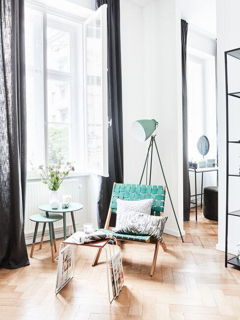 Fotel, stoliki i lampa w odcieniach mięty przy dużym oknie w salonie