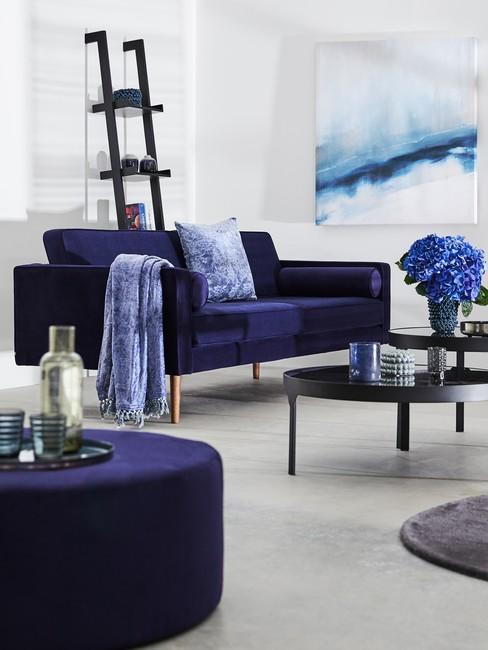 Biały salon z kobaltową sofą, pufem oraz błękitnymi dodatkami