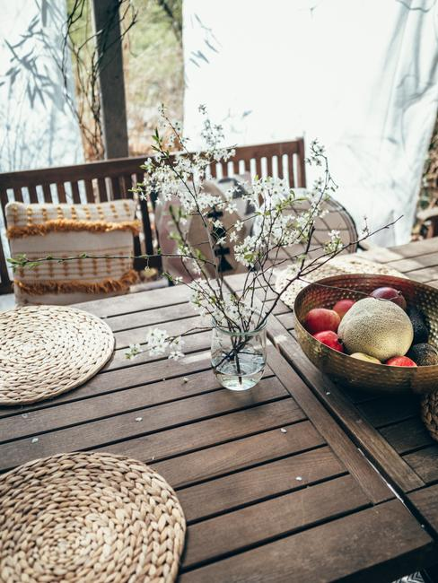 Drewniane meble i boho poduszki na tarasie urządzonym przez Travelicious