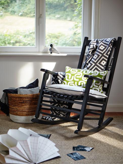 Fragment pomieszczenie z czarnym fotelem bujanym, koszem i dywanem z juty