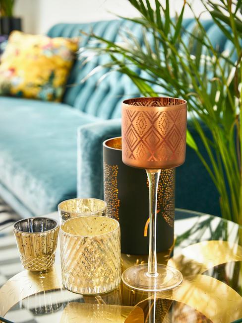 Stolik kawowy ze świecznikami oraz dużą rośliną w donicy.
