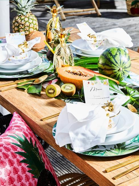 Stół na przyjęcie w stylu tropikalnym z wzorzystymi talerzami oraz owocami jako dekoracje