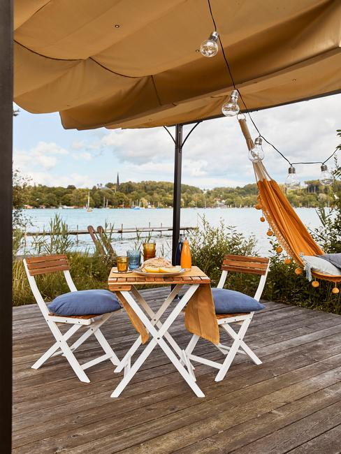 Zbliżenie na drewniany sotlik ogrodowy z dwoma krzesłami