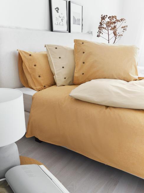Biała sypialnia z łożkiem z lekko pomarańczową pościelom oraz poduszkami