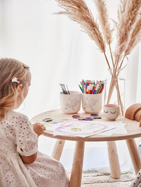 Dziewczynka siedząca przy drewnianym stole