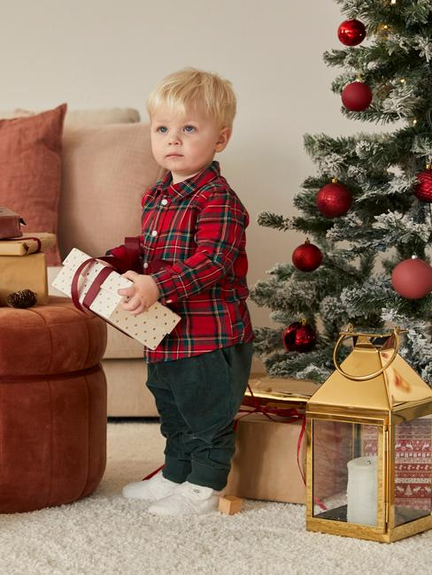 Chłopczyk stojący przy złotej latarance oraz czerwonym pufie