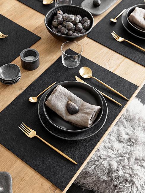 Stół jadalny z czarną i złotą zastawą