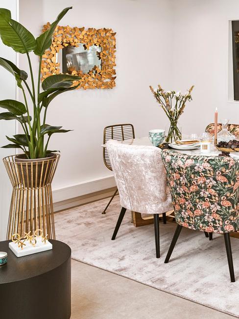 Wnętrze jadalni z lustrem w złotej ramie, różnie obytymi krzesłami, rosliną w wazonie oraz dywanem