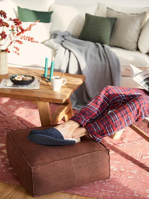 Salon z biała sofą, brązowym pufem i czerwonym dywanem