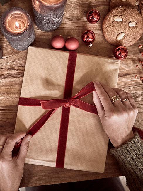 Pakowanie prezentu w beżowy paier z czerwoną wstążką