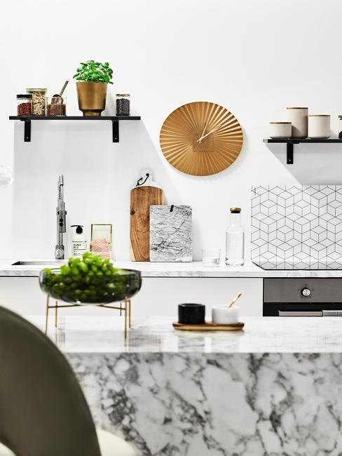 Biała kuchnia z marmurową wyspą kuchenną, ro slinami oraz dekoracjami na ścianie
