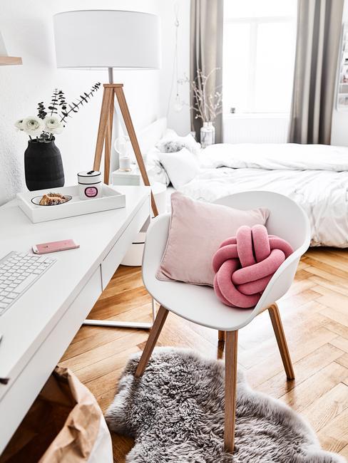 Biała sypialnia z łożkiem, białym biurkiem, krzesłem oraz poduszkami
