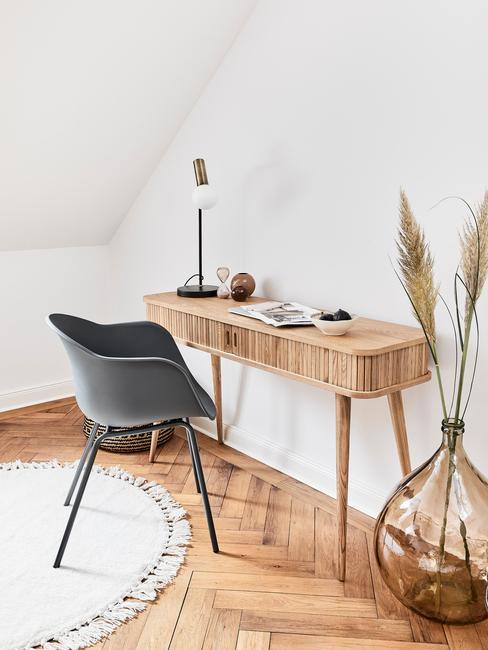 Białe wnętrze z drewnianym biurkiem, szarnym krzesłem, wazonem oraz suszoną kompozycją