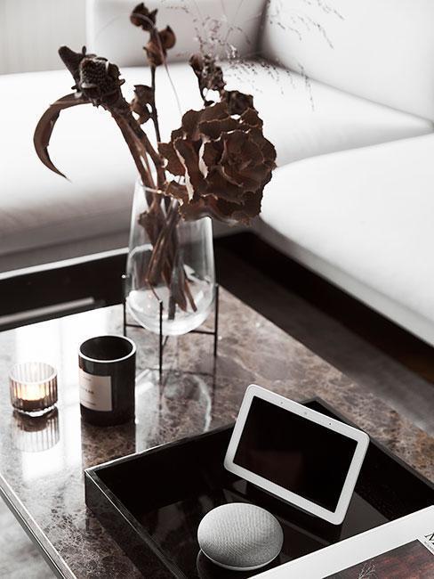 Zbliżenie na stolik kawowy w salonie ze szklanym wazonem, sztucznymi kwiatami, czarną tacę dekoracyjną i elektroczną ramką