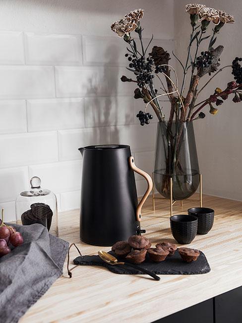 Zbliżenie na drewniany blat w kuchni z czarnym czjjnikiem, filiżankami, szklanym wazonem z kwiatami i taca