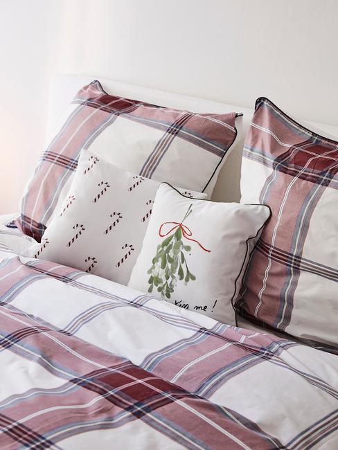 Zbliżenie na pościel w kratę na łożku oraz poduszki dekoracyjne w świąteczne wzory