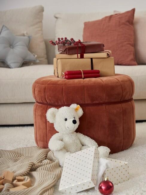 Zbliżenie na brązowy puf z prezentami, białym misem na dywanie