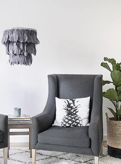 Wnętrze salonu z szarym fotele z poduszką, dywanem i lampą DIY w stylu boho