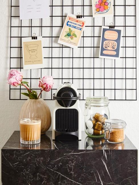 Nahaufnahme Kaffeeecke mit Kaffeemaschiene und Gitter-Pinnwand darüber
