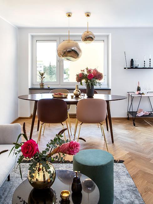 Essbereich in wohnzimmer mit Fischgrätenparkett, dunklem Esstisch und rosa Akzenten