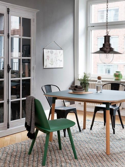Stühle in verschiedenen Farben an einem Tisch mit Holzbeinen auf einem Teppich