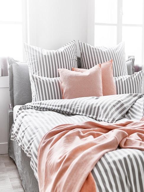 Cama de matrimonio con set de ropa de cama en tonos grises y rosas.