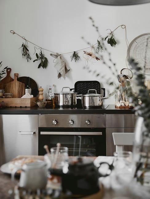 Backofen hinter einem gedeckten Esstisch, darauf und daneben Küchenutensilien