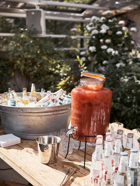 Getränkespender aus Glas mit Tomatensaft auf einer Anrichte