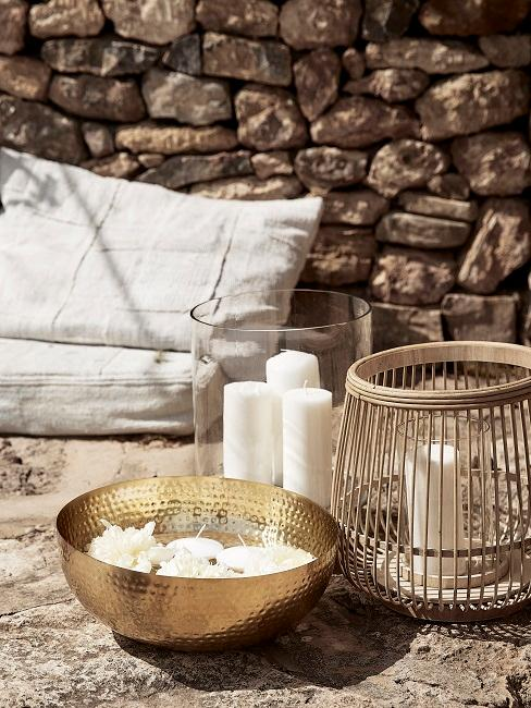 Kerzendeko und Kissen auf einem Steinboden vor einer Mauer outdoor