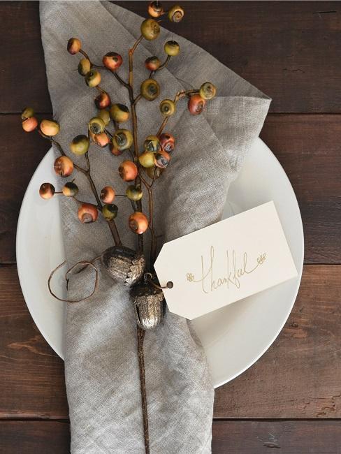 """Teller auf einem Holztisch, darauf eine Serviette mit einem Beerenzweig und einem kleinen Zettel mit """"thankful""""-Aufschrift"""