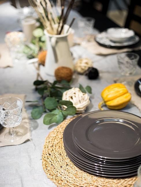 Gedeckter Tisch mit herbstlicher Erntedank Deko wie Kürbissen und Blättern