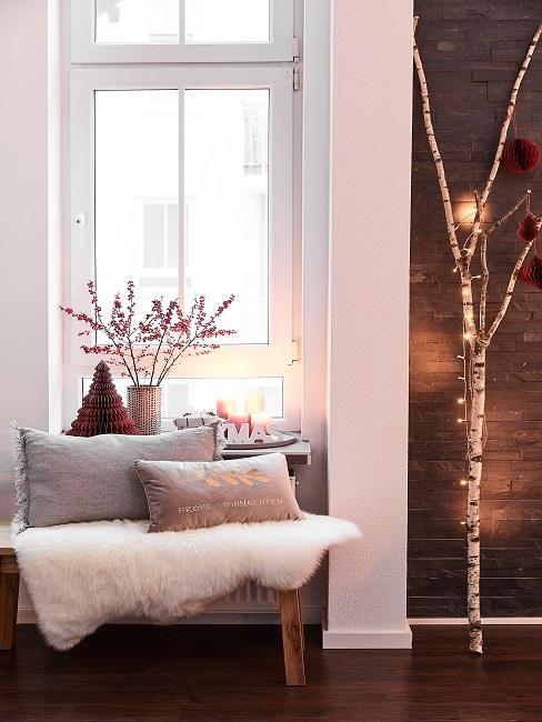 Gemütliche Sitzbank mit Kissen und Fell vor einem Fenster mit weihnachtlicher Deko, daneben ein Baumstamm mit Lichterkette