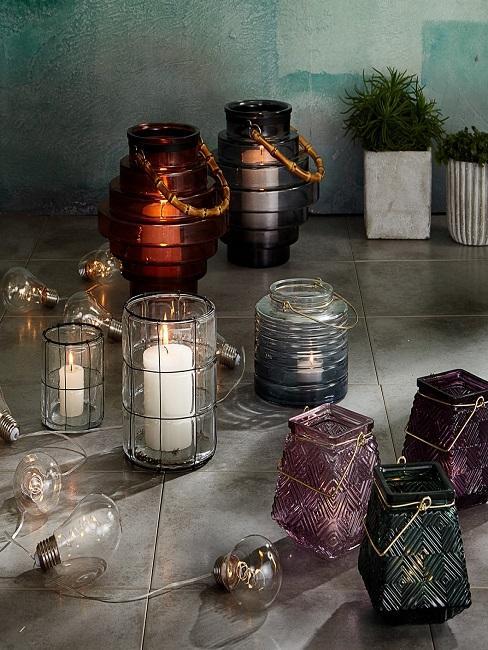 Beton Übertöpfe stehen auf dem Boden neben Kerzen in transparenten Windlichtern.