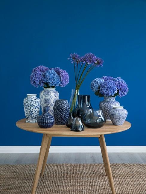 Kleiner Tisch aus Holz mit sehr vielen Vasen und Blumen in Blautönen