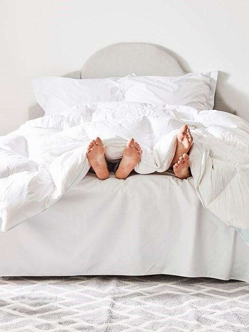 Füße unter weißer Bettwäsche