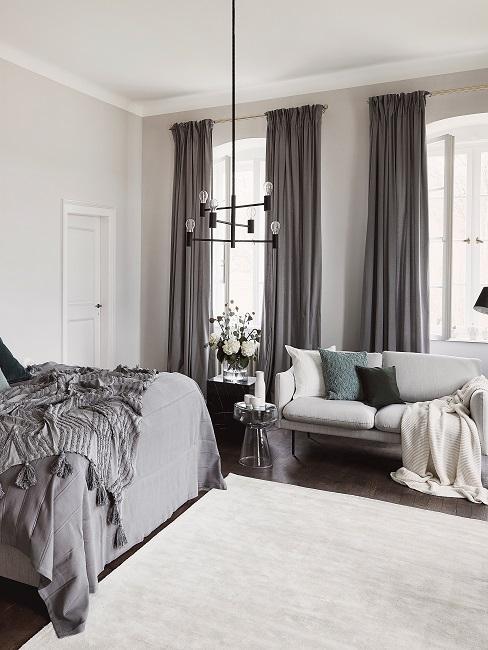 Schönes Zimmer graues Schlafzimmer mit Sofa, schwarzer Leuchte und weißem Teppich