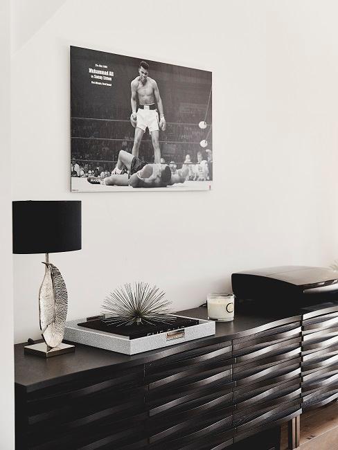 EIn schwarzes Sideboard mit wenig Deko, darüber ein schwarz-weiß Bild