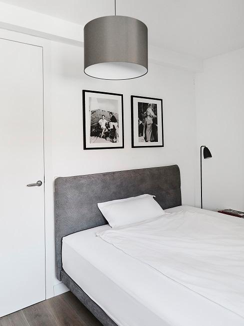 Ein weißes Schlafzimmer mit grauem Bett und grauer Lampe sowie zwei Wandbildern im minimalistischen Stil