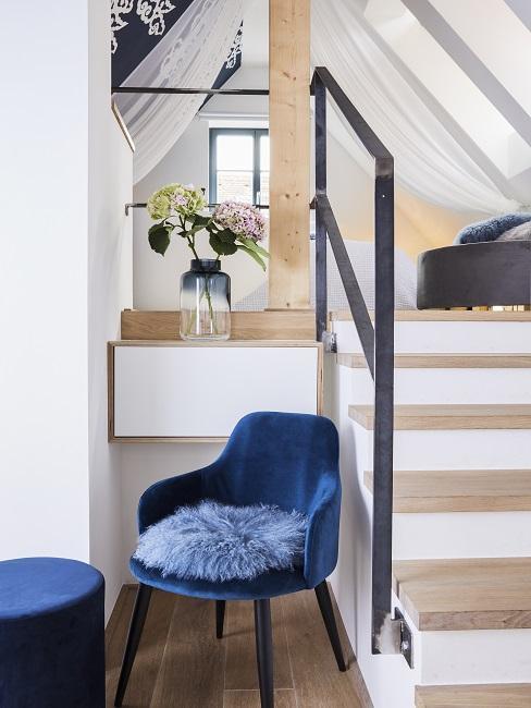 Treppenhaus gestalten mit blauem Sessen und Fellkissen