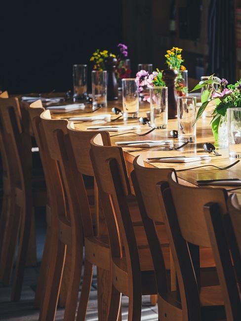 Langer Holztisch mit cleaner Deko durch Glasvasen und bunte Blümchen