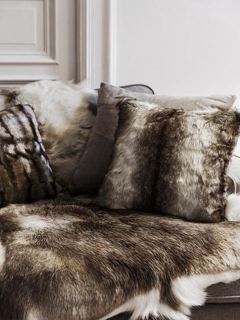Sessel mit vielen Fellen und Fellkissen im Wohnraum.